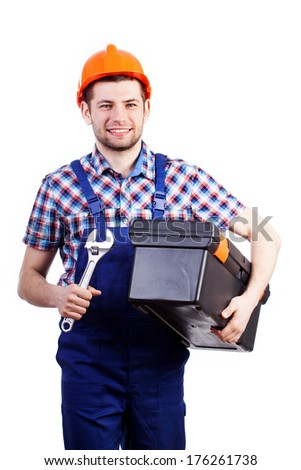 Young happy handyman in blue overalls walking with wrench and toolbox - stock photo