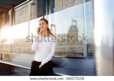 Young happy hipster girl with beautiful smile tells via mobile phone her friend about her unforgettable vacation, gorgeous cheerful woman in good mood calling via cell telephone while sitting outdoors - stock photo