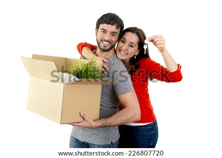 young happy Hispanic couple moving together in a new house , flat or apartment carrying cardboard boxes home belongings smiling in housing and real state concept - stock photo