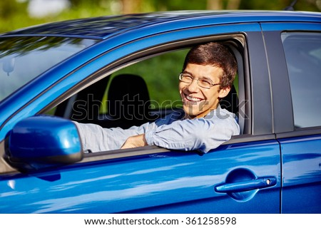 Young happy hispanic man wearing glasses and blue jeans shirt sitting behind wheel of his car and smiling through window - new drivers concept - stock photo
