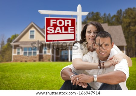 Young Happy Hispanic Young Couple in Front of Their New Home and For Sale Real Estate Sign. - stock photo
