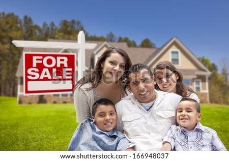 Young Happy Hispanic Young Family in Front of Their New Home and For Sale Real Estate Sign.