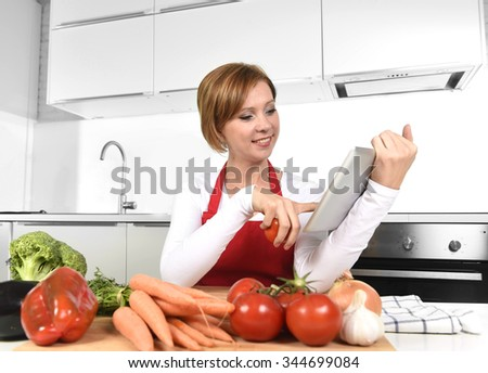 young happy home cook woman in red apron at domestic kitchen using digital tablet as recipe reference and cookbook with vegetables at the table in healthy nutrition and technology cooking help - stock photo