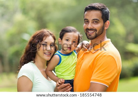 young happy indian family with the kid outdoors - stock photo