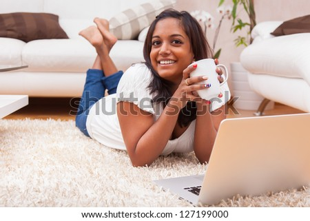 Young happy indian lying down on the floor woman using a laptop