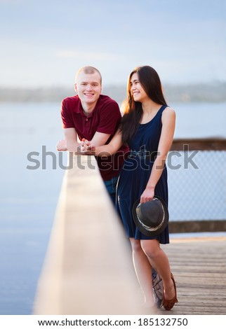 Young happy interracial couple standing together on wooden pier overlooking lake - stock photo