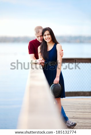 Young happy interracial couple standing together on wooden pier overlooking lake. Man bowing head in prayer. - stock photo