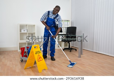 Young Happy Janitor Cleaning Floor With Wet Floor Sign - stock photo