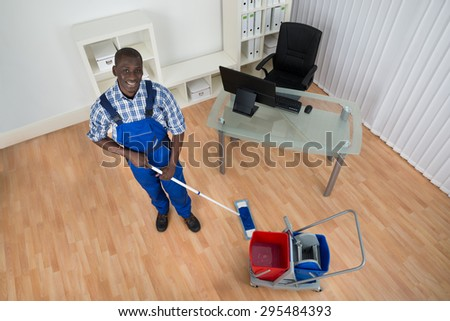 Young Happy Janitor Cleaning Floor With Wet Floor Sign