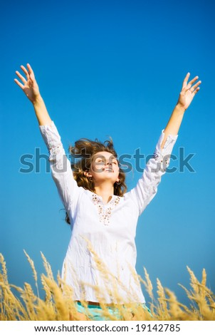 Young happy jumping woman. On blue sky background.