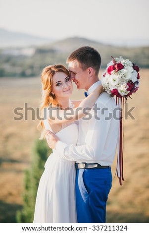 Young happy just married couple posing on the top of the mountain. Wedding day