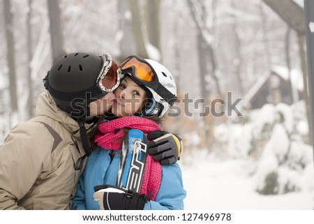 Young happy kissing couple in winter - stock photo