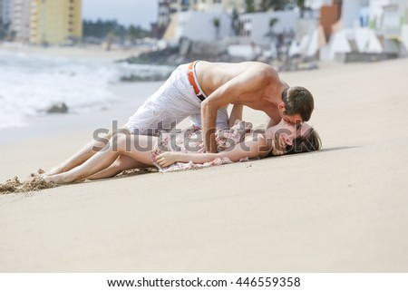 Young happy kissing couple on ocean beach, laying on sand. Romance concept and positive human emotions.