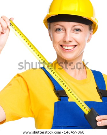 Young happy lady as a construction worker with tape measure, isolated over white - stock photo