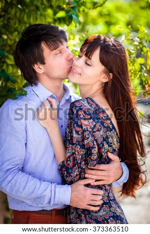 Young happy love couple relaxing in park - stock photo