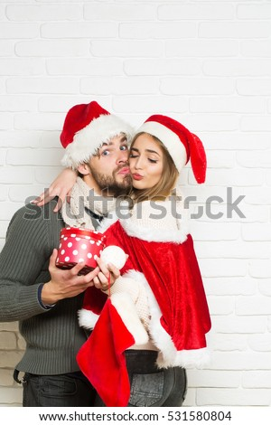 Young happy loving Christmas couple in red santa claus hats of man with gift box and pretty sexy girl or beautiful woman kissing on white brick wall