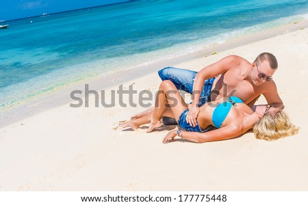 young happy loving couple on beach, tropical background