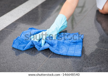 Young Happy Maid Cleaning The Floor With Cloth - stock photo