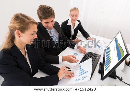 Young Happy Male And Female Businesspeople Working On Graphs In Office