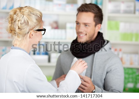 Young happy male customer buying medicine at the pharmacy - stock photo