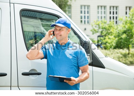 Young Happy Male Worker In Front Of Truck Writing On Clipboard - stock photo