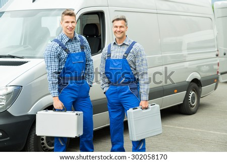 Young Happy Male Worker With Toolbox Standing In Front Of Van - stock photo
