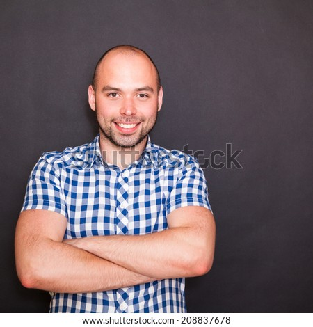 Young happy man against the black background - stock photo