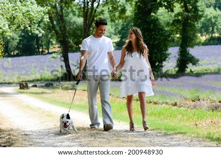 young happy man and woman couple walking with their dog in summer vacation in countryside - stock photo