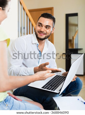 Young happy man and woman with business papers and laptop