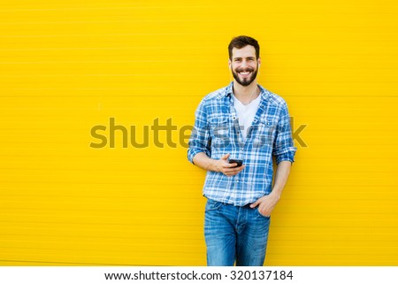 young happy man casual dressed with headphones and smart phone on yellow background