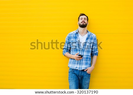 young happy man casual dressed with headphones and smart phone on yellow background, listening music and relaxing - stock photo