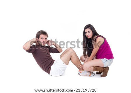 Young happy man doing situps with beautiful personal trainer isolated on white - stock photo