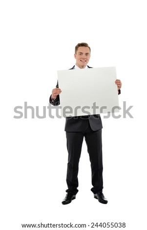 Young happy man dressed with suit holding white empty paper isolated on white background.  - stock photo
