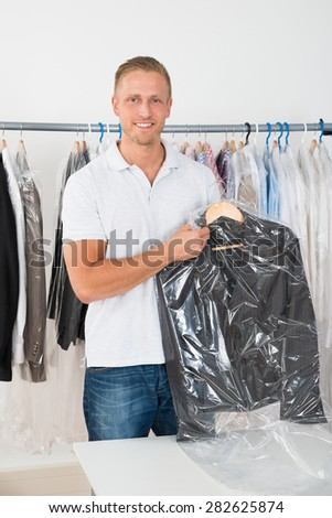 Young Happy Man Holding Coat In Dry Cleaning Store - stock photo
