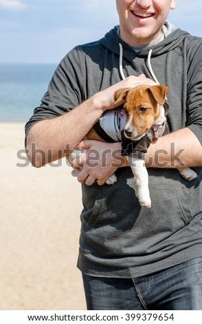 Young happy man holding his cute small dog Jack Russell terrier on beach - stock photo