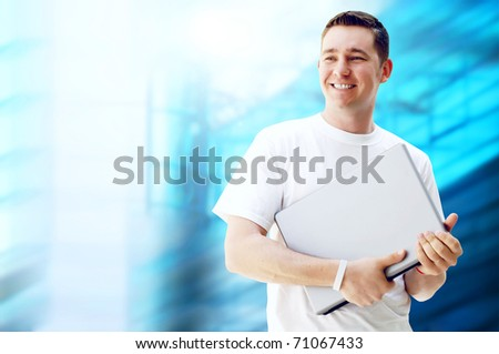 Young happy man or student with laptop and phone on the business background