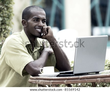 Young happy man or student with laptop sitting at the table - stock photo