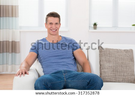 Young Happy Man Sitting On Sofa In Living Room - stock photo