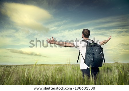 Young happy man standing on a wheat field