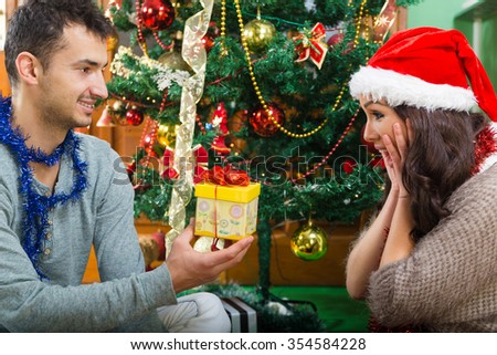 Young happy man surprises his girlfriend with Christmas gift , Surprise present on New Year holiday by Xmas tree at home , Family happiness and couple in love concept - stock photo