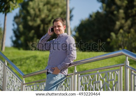 Young, happy man talking mobile phone and standing on the stairs in a park