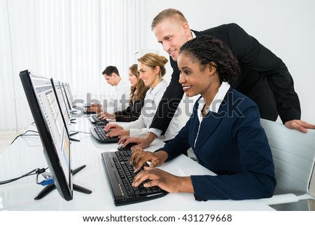 Young Happy Manager Assisting His Female Staff In Office