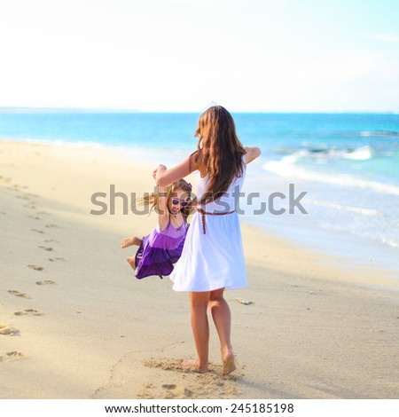Young happy mother and adorable daughter having fun at exotic beach on sunny day - stock photo