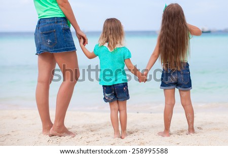 Young happy mother and adorable daughters at white beach on sunny day - stock photo