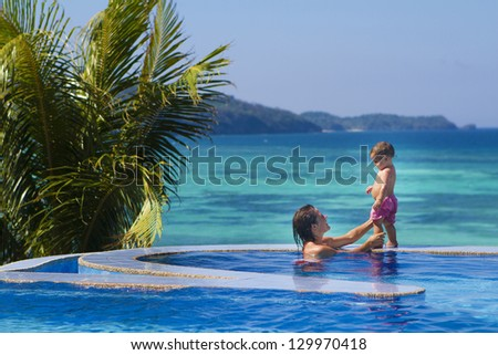 young happy mother and baby enjoying vacation in swimming pool on tropical sea background - stock photo