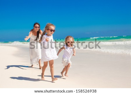 Young happy mother and her adorable daughters having fun at exotic beach on sunny day - stock photo
