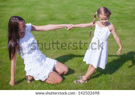 Young happy mother and her daughter having fun in the yard - stock photo