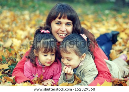 Young happy mother and her daughters play in autumn park - stock photo