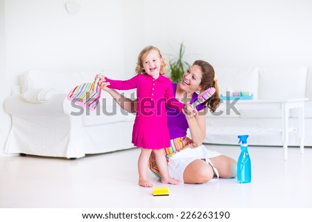 Young happy mother and her little daughter, cute toddler girl, cleaning the house together sweeping the floor in a white sunny living room with modern interior and big white couch - stock photo