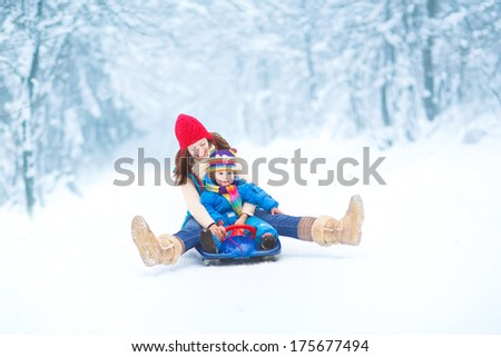 Young happy mother and her little toddler daughter enjoying a sledge ride in a beautiful snowy winter park - stock photo